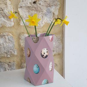 Papieren vaasje voor het voorjaar met aquarel eitjes in roze met narcissen erin